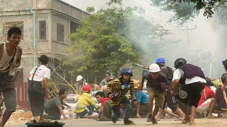 FILE PHOTO. Protesters take cover during clashes with security forces in Monywa, Myanmar on March 21, 2021.