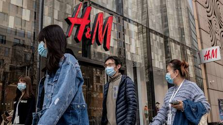People walk past a store of Swedish clothing giant H&M in Beijing on March 25, 2021. © AFP / NICOLAS ASFOURI