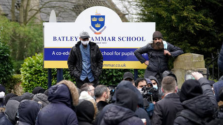 Protesters gather outside the Batley Grammar School in Batley, Britain, March 26, 2021. © Christopher Furlong / Getty Images