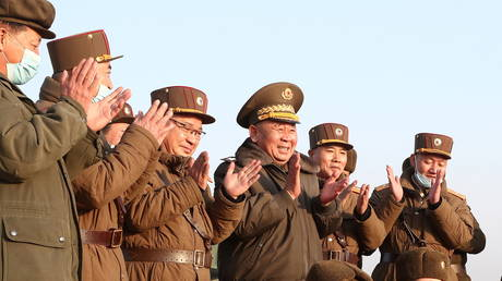 Ri Pyong Chol, the senior leader who is overseeing the test, and other military officials applaud after the launch of a newly developed new-type tactical guided projectile on March 25, 2021© KCNA/Reuters