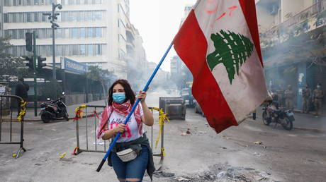 A demonstrator carries a national flag along a blocked road, during a protest against the fall in Lebanese pound currency and mounting economic hardships, near the Central Bank building, in Beirut, Lebanon (FILE PHOTO) © REUTERS/Mohamed Azakir