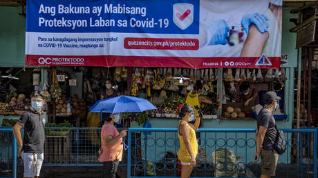 A streamer showing information on COVID-19 vaccines is seen as Filipinos queue outside a wet market to stock up on food a day before a strict lockdown is reimposed in Manila and nearby provinces on March 28, 2021 in Quezon city, Metro Manila, Philippines.