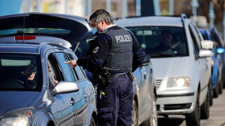 A police officer checks commuters in a car arriving from Poland, at the German-Polish border crossing Stadtbruecke (city bridge) amid the coronavirus disease (COVID-19) outbreak, in Frankfurt (Oder), Germany, March 22, 2021.