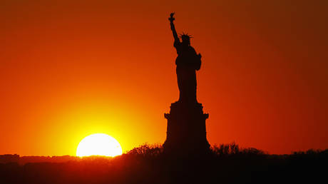 FILE PHOTO: The sun sets behind the Statue of Liberty in New York, May 26, 2013