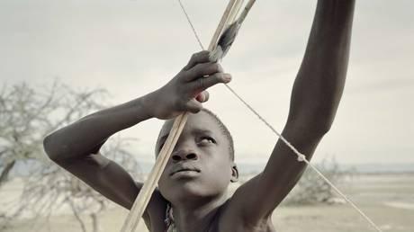 Manu, 14, of the Hadza tribe in Tanzania shoots an arrow.© Global Look Press via ZUMA Press