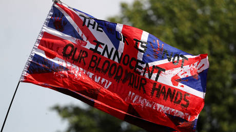 FILE PHOTO: A British national flag, known as the Union Jack, with writing on it flutters during a Black Lives Matter protest outside Tottenham police station in London, Britain August 8, 2020