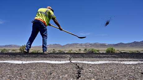 A crack across the roadway is seen as Nevada Department of Transportation worker repairs damage to US Highway 95 after a strong earthquake struck near Tonopah, Nevada, US