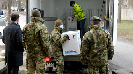 FILE PHOTO. Hungarian soldiers unload a truck with the first shipment of Pfizer-BioNTec vaccines against the novel coronavirus (Covid-19) at the South-Pest Central Hospital in Budapest on December 26, 2020. © AFP / SZILARD KOSZTICSAK