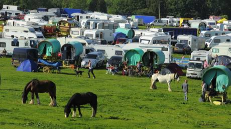 Horses graze in a field next to travellers during the horse fair in Appleby in Westmorland, Cumbria