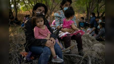 FILE PHOTO: Migrant women from Honduras are shown holding their children after crossing the Rio Grande River on rafts into the US on March 26.