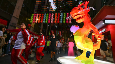 FILE PHOTO: People walk past a large illuminated lantern resembling a dragon in Chinatown during Lunar New Year Celebrations, as the Coronavirus (COVID-19) pandemic continues, in Sydney, Australia, on February 12, 2021