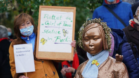 FILE PHOTO: Protesters rally near a statue in Berlin, Germany, dedicated to WWII-era Korean 'comfort women,' October 2020. © Sean Gallup / Getty Images