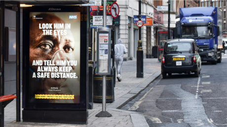 FILE PHOTO. A Look him in the eyes and tell him you always keep a safe distance poster seen at Leicester square station. England remains under lockdown as the government battles to keep the coronavirus pandemic under control. © Getty Images / Dave Rushen