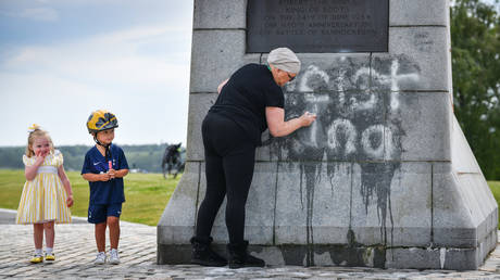 """FILE PHOTO: Children look on as a member of the public cleans the Robert the Bruce Statue which has been defaced with graffiti saying """"Racist King"""" on June 12, 2020 in Bannockburn, Scotland"""