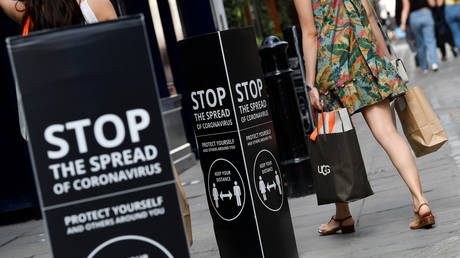 Shoppers walk past social distancing signs at the Covent Garden shopping and dining district, amid the spread of the coronavirus disease (COVID-19), in London, Britain, August 2, 2020.