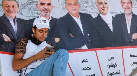 FILE PHOTO. A man browses a phone while sitting and leaning onto a campaign poster in Jordan's capital Amman. ©KHALIL MAZRAAWI / AFP
