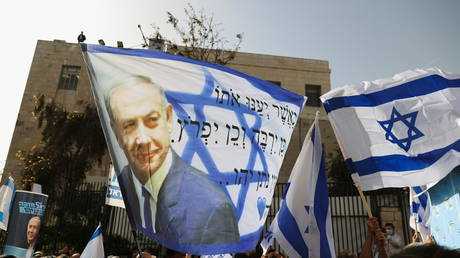 Supporters of Israeli Prime Minister Benjamin Netanyahu, wave an Israeli flag with an image of Netanyahu, as his corruption trial resumes, near Jerusalem's District Court (FILE PHOTO) © REUTERS/Ronen Zvulun