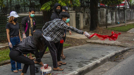 Anti-coup protesters throw red paint on a street during a demonstration in Yangon, Myanmar, Tuesday April 6, 2021.