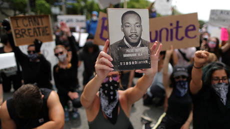 FILE PHOTO: A demonstrator holds a picture of Martin Luther King Jr. during a protest against the death in Minneapolis police custody of George Floyd, in Los Angeles, California, US June 2, 2020