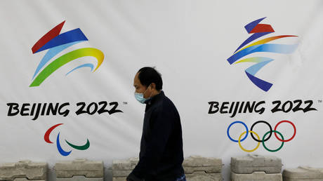 FILE PHOTO: A man walks past a board with logos of the 2022 Winter Olympic Games in Beijing, China, January 29, 2021 © Reuters / Tingshu Wang