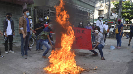 Anti-coup protesters burn a Chinese flag during a demonstration in Yangon, Myanmar on Wednesday, April 7, 2021.