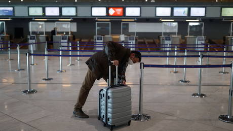 A passenger waits for check-in in the departures area of the Terminal 2E at Charles-de-Gaulle airport in Roissy, France