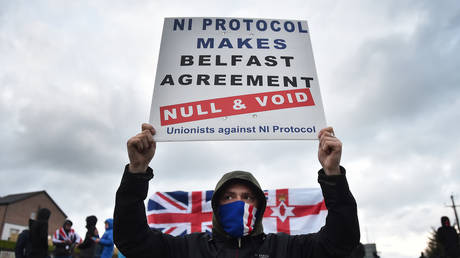 Loyalists hold up placards during an anti Northern Ireland Protocol protest against the so called Irish Sea border on April 6, 2021 in Larne, Northern Ireland.