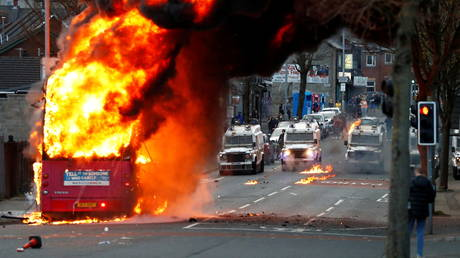 Police vehicles behind a hijacked bus burning on the Shankill Roadin Belfast, Northern Ireland, April 7, 2021