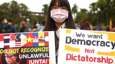 A woman holds up posters against the Myanmar military coup during a Milk Tea Alliance united rally in Taipei, Taiwan, February 28, 2021 © Reuters / Ann Wang