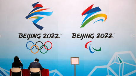 "FILE PHOTO: Staff members sit near a board with signs of the 2022 Olympic Winter Games, at the National Aquatics Center, known colloquially as the ""Ice Cube"", in Beijing, China April 1, 2021"