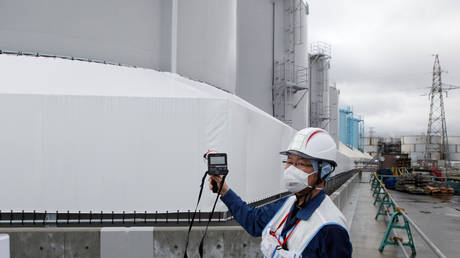 An employee of Tokyo Electric Power Co's (TEPCO) uses a geiger counter next to storage tanks for radioactive water at TEPCO's tsunami-crippled Fukushima Daiichi nuclear power plant in Okuma town, Fukushima prefecture, Japan (FILE PHOTO) © REUTERS/Aaron Sheldrick