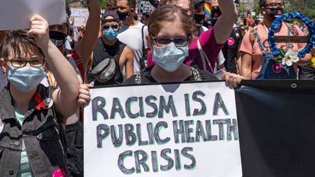 FILE PHOTO: A participant holds a placard that says Racism is a public health crisis in Foley Square during the Queer Liberation March hosted by The Reclaim Pride Coalition for Trans and Queer black lives against police brutality in lower Manhattan