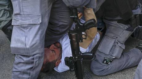 Israeli MP Ofer Cassif is held down by police during a demonstration against Israeli occupation and settlement activity in the Palestinian Territories and east Jerusalem on April 9, 2021 © Ahmad Gharabli/AFP