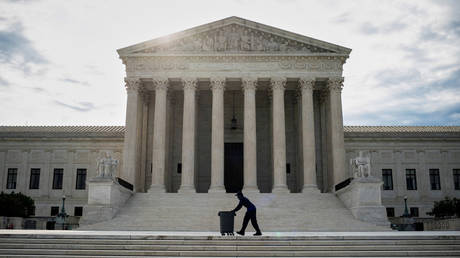 FILE PHOTO: A man wheels trash bins past the US Supreme Court building in Washington, DC, June 25, 2020 © Reuters / Al Drago