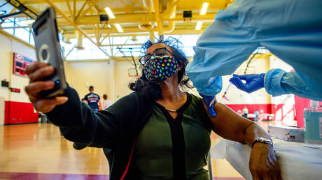 A women takes a selfie while receiving a dose of Moderna COVID-19 vaccine on Jan. 14, 2021.