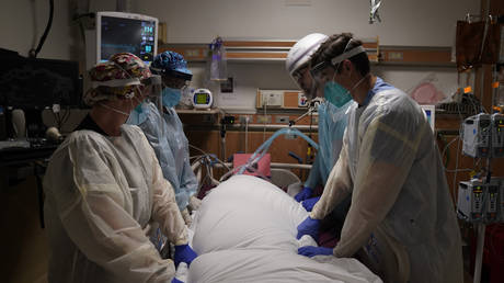 FILE PHOTO: Medical workers prepare to manually prone a COVID-19 patient in an intensive care unit at Providence Holy Cross Medical Center in the Mission Hills section of Los Angeles.
