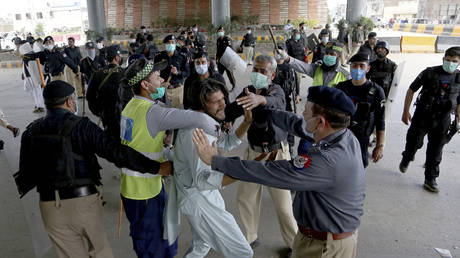 Police officers detain a supporter of Tehreek-e-Labiak Pakistan, a radical Islamist political party, at a protest against the arrest of their party leader, Saad Rizvi, in Peshawar, Pakistan, Tuesday, April 13, 2021.