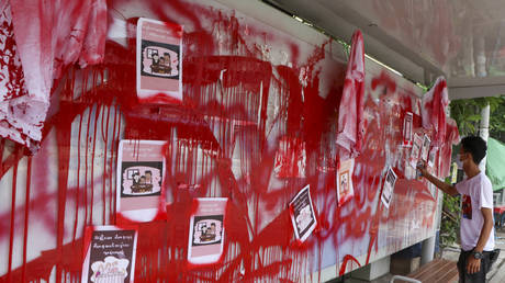 An anti-coup protester uses red paint as he writes slogans at a bus stop on Wednesday April 14, 2021 in Yangon, Myanmar.