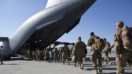 US Army soldiers walk to their C-17 cargo plane for departure May 11, 2013 at Bagram Air Base, Afghanistan.