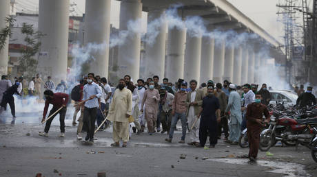 Angry supporters of Tehreek-e-Labiak Pakistan, a radical Islamist political party, throw stones towards police firing tear gas to disperse them, at a protest against the arrest of their leader Saad Rizvi, in Lahore, Pakistan, Monday, April 12, 2021.