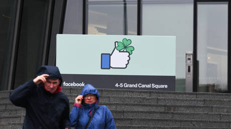 People pass in front of the European HQ of Facebook on the eve of St Patrick's Day celebrations. On Saturday, March 16, 2019, in Dublin, Ireland.