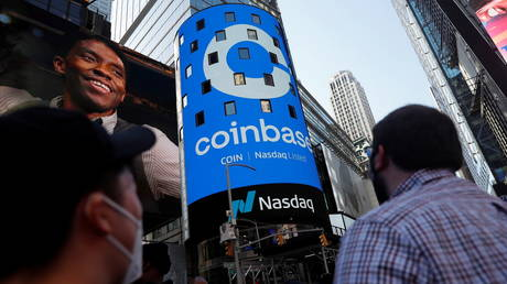 FILE PHOTO: People watch as the logo for Coinbase is displayed on the Nasdaq MarketSite jumbotron at Times Square in New York, US, on April 14, 2021