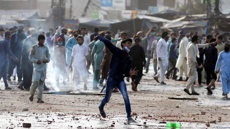 A supporter of the Tehreek-e-Labaik Pakistan (TLP) Islamist political party hurls stones towards police (not in picture) during a protest against the arrest of their leader in Lahore, Pakistan (FILE PHOTO) © REUTERS/Stringer