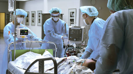 In the Covid ward, an area of the Operative Intensive Care Unit of Leipzig University Hospital, a patient is driven to a CD by doctors and nurses with connected devices.