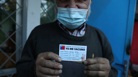 A homeless man shows an ID reading 'I've been vaccinated' after receiving a dose of Sinovac's CoronaVac coronavirus disease (Covid-19) vaccine during a vaccination campaign for homeless people, in Santiago, Chile (FILE PHOTO) © REUTERS/Ivan Alvarado