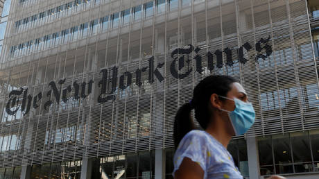 A woman wearing a protective face mask walks by the New York Times building in Manhattan