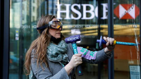 An activist from the Extinction Rebellion smashes a window at HSBC headquarters during a protest in Canary Wharf, London, Britain on April 22, 2021.