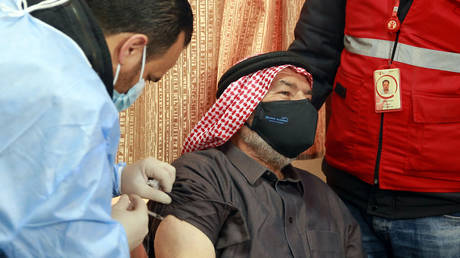 A mask-clad Jordan-based Syrian refugee receives a vaccination dose against COVID-19 coronavirus disease at a governmental medical center in Mafraq in northern Jordan on January 18, 2021.