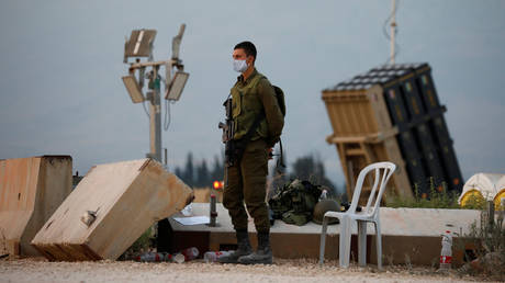 An Israeli soldier stands guard next to an Iron Dome anti-missile system near the Israel's northern border with Lebanon July 27, 2020.