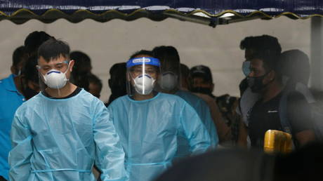 Personnel in protective garment usher a group of migrant workers after workers tested positive for the coronavirus disease (Covid-19) at Westlite Woodlands dormitory in Singapore (FILE PHOTO) © REUTERS/Edgar Su